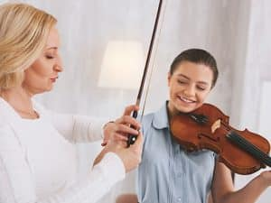 Home education. Pleased girl feeling happiness while having lesson of classical music